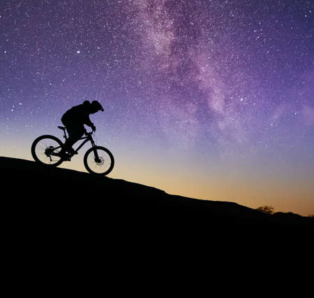 Cyclist Riding the Bike on the Rock Under the Night Sky. Sport Lifestyle and Adventure Concept.