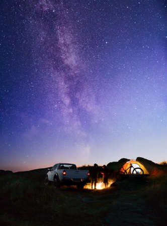 Friends near Bonfire, Pickup Truck, Tent and Bike in the Mountains under Night Sky with Milky Way. Adventure and Travel