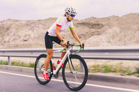 Young Woman Cyclist Riding Bike on the Mountain Road. Adventure, Healthy Lifestyle, Sport Imagens