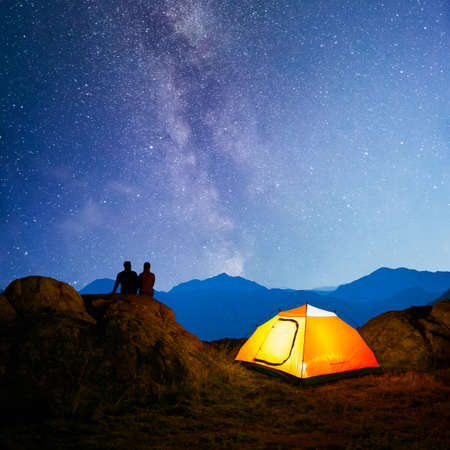 Young Couple Sitting on the Rock near Illuminated Tent and Watching the Bright Milky Way Above the Beautiful Mountains Imagens