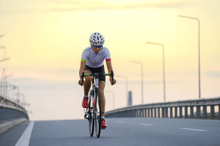 Young Woman Cyclist Riding Road Bike at Sunset. Adventure, Healthy Lifestyle, Sport Imagens