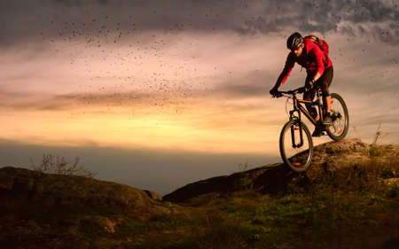 Cyclist in Red Riding Bike on the Autumn Rocky Trail at Sunset. Extreme Sport and Enduro Biking Concept.