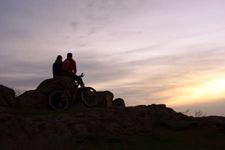Young Couple Sitting on the Rock in the Mountains at Night