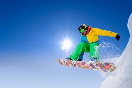Snowboarder Jumping on Snowboard in the Mountains. Snowboarding and Winter Sports Banque d'images