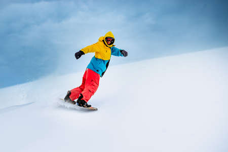 Snowboarder Riding Snowboard in the Mountains. Snowboarding and Winter Sports