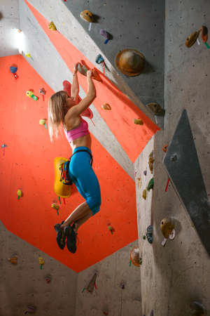 Young Woman Climber Bouldering in the Climbing Gym. Extreme Sport and Indoor Climbing Concept Imagens