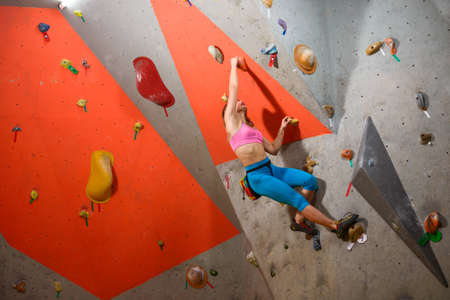 Climbing Gym. Young Woman Climber Bouldering. Extreme Sport and Indoor Climbing Concept