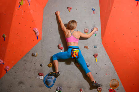 Woman Climber Practicing Rock-climbing in the Bouldering Gym. Extreme Sport and Indoor Climbing Concept
