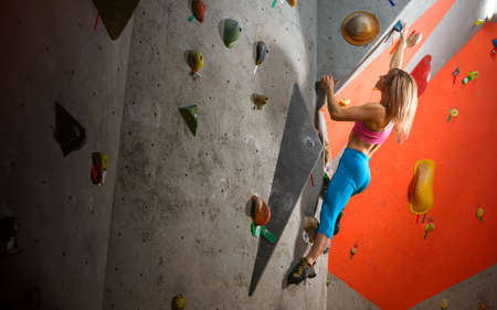 Beautiful Woman Climber Bouldering in the Climbing Gym. Extreme Sport and Indoor Climbing Concept
