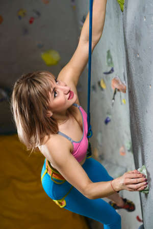 Beautiful Smiling Woman Climber Bouldering in the Climbing Gym. Extreme Sport and Indoor Climbing Concept