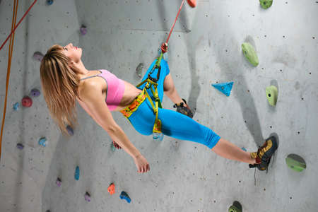 Young Woman Climber Relaxing on the Belay in Climbing Gym. Extreme Sport and Indoor Climbing Concept