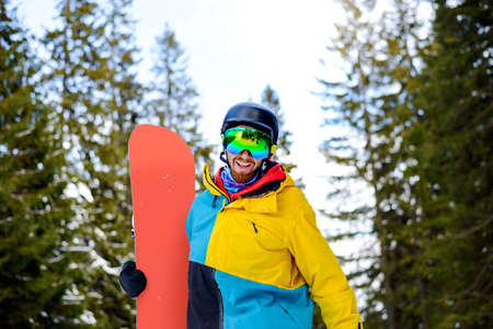 Portrait of Young Snowboarder with the Snowboard in the Winter Forest. Snowboarding and Winter Sports