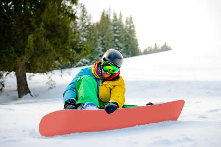 Snowboarder Getting Ready for Riding Snowboard in the Mountains. Snowboarding and Winter Sports
