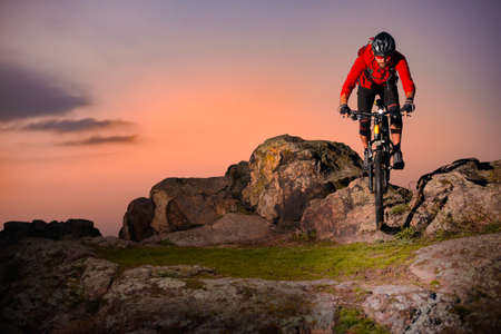 Cyclist in Red Riding Bike on the Spring Rocky Trail at Sunset. Extreme Sport and Enduro Biking Concept.
