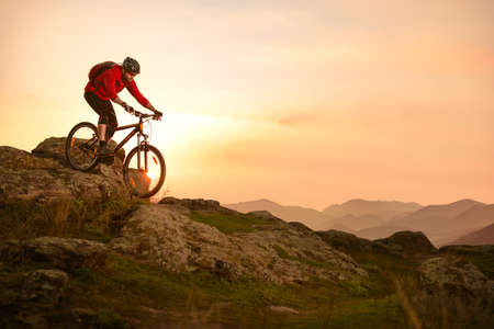 Cyclist in Red Riding Bike on the Summer Rocky Trail at Sunset. Extreme Sport and Enduro Biking Concept.