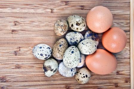 perdrix: Oeufs de poule, la perdrix et les cailles sur le bois Banque d'images