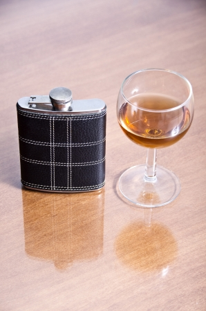 photo of a cup of brandy and pocket bottle  photo