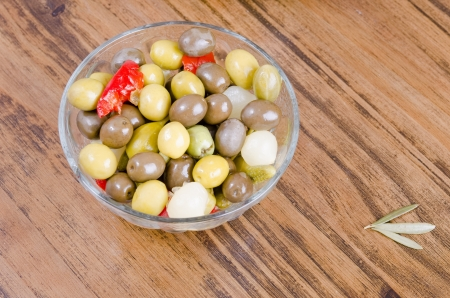 Olives and pickles on wood table photo