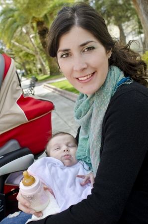 nursing bottle: Mother and baby outdoors  Stock Photo