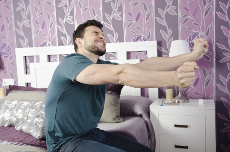 grinding teeth: Stretching man who has risen early in a bedroom  Stock Photo
