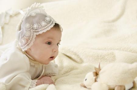 battesimo: Piccolo bambino con cappuccio cereminial sdraiato Archivio Fotografico