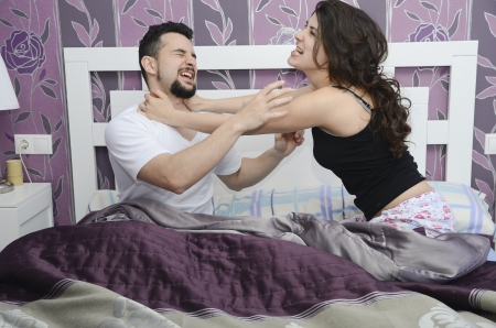 choking: Discusses couple in bed, a fight that symbolizes marital conflicts  Stock Photo