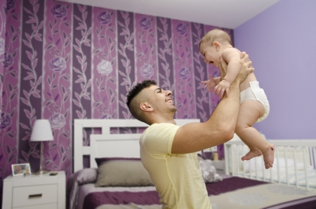 Modern and young father with baby in bedroom. photo