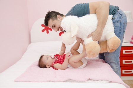 Father with big muppet playing with baby photo