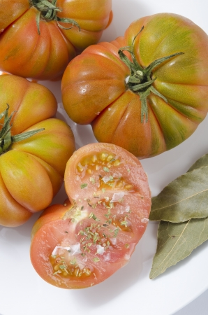 grocers: Spanish raff tomatoes and laurel leaf on saucer Stock Photo