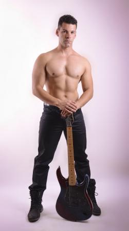 nudo maschile: Posa ragazzo forte con chitarra rock sullo sfondo di studio