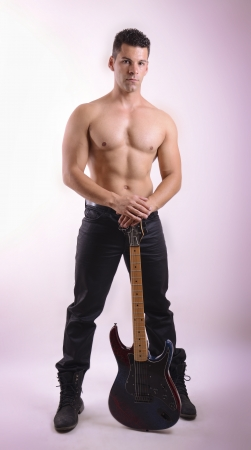 nude male: Posing strong guy with rock guitar on studio background