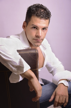 Portrait of seductive man on chair looking at the view  photo
