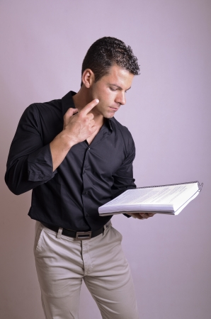 reciting: Man reading book, may be a student or an actor.