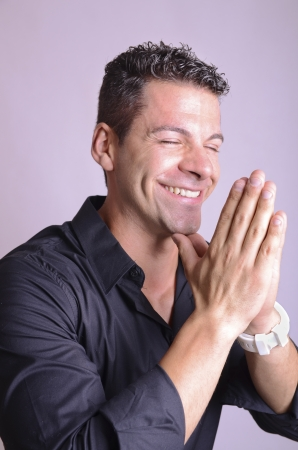 Man smiling with his hands in prayer position. photo