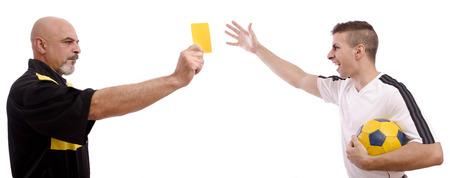 arbitros: Advertir: Tarjeta amarilla para el jugador de fútbol. Chicos aislados en blanco. Foto de archivo