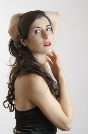 Brunette girl in studio posing looking out of frame  photo