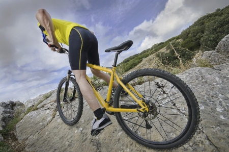 Cyclist climbing rocks with his bike in wide angle portrait  photo