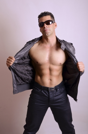 young man jeans: Sexy man with sunglasses show abs in studio shot.  Stock Photo