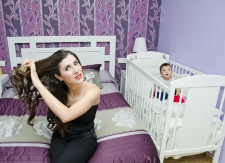 Young mother combing hair with baby in crib. photo