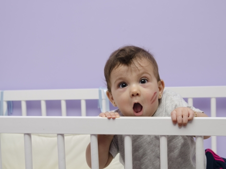 disheveled: Fun baby with kiss mark on cradle in home bedroom.