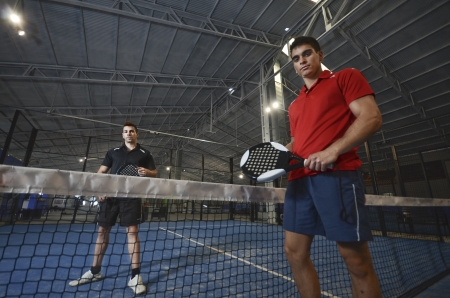 Paddle tennis couple posing in blue turf photo