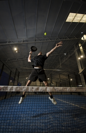 Paddle tennis couple posing in blue turf, attack position, smashing. Banque d'images