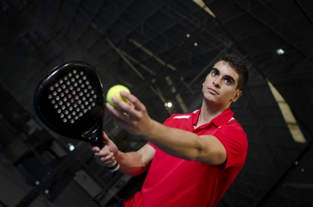 Paddle tennis player in court ready for serve. photo