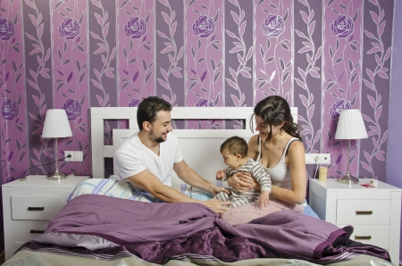 Happy young couple with their baby in the bedroom photo