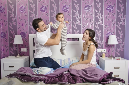Young parents in home bedroom lifting baby photo
