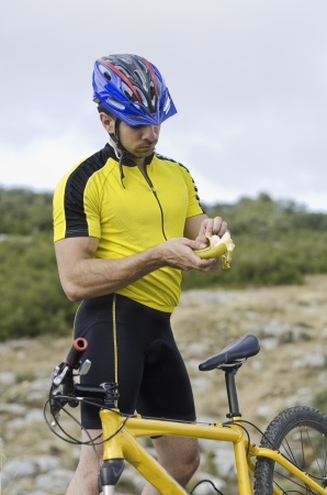 eating banana: Mountain bike sport: cyclist eating banana looking for potassium Stock Photo
