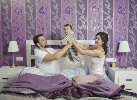 fathera and mother in home bedroom lifting baby. photo