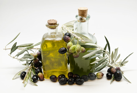 extra: Olive oil: extra and virgin in glass bottle with olives. Stock Photo