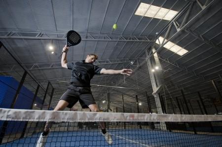 パドルのテニス選手とボール破りジャンプ