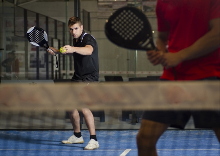 Paddle tennis couple ready for serve indoor. photo